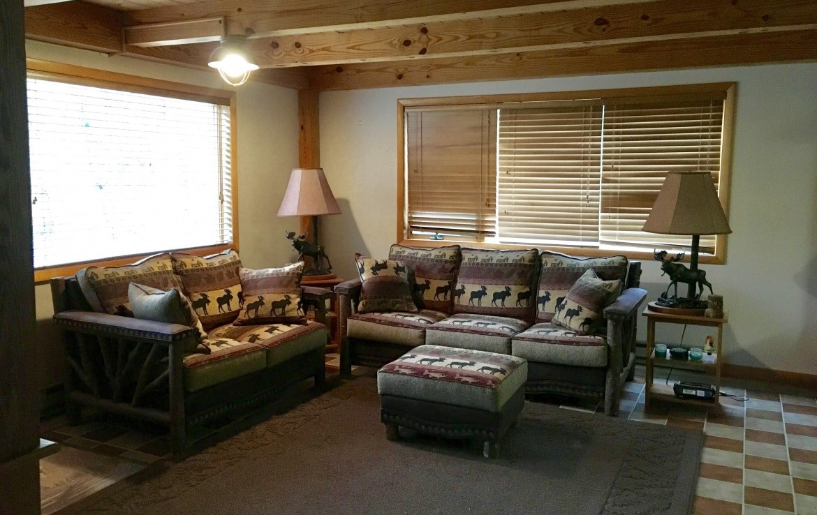 interior is finished with beautiful exposed wooden beams, tile floors and rustic Adirondack accents