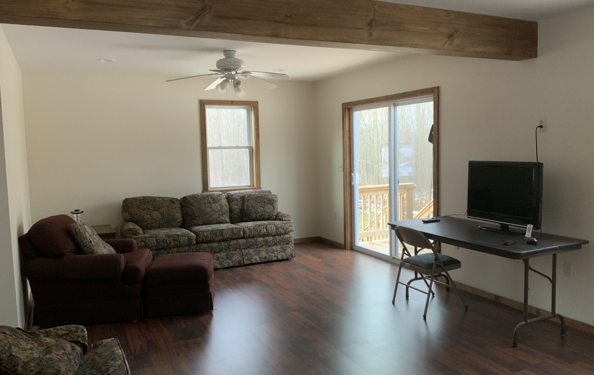 First-floor living room with large deck overlooking woodlands (second deck leading out of the man door).